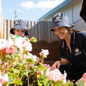 A Child Outside Looking at Flowers With a Teacher - Cannon Hill Early Learning Centre